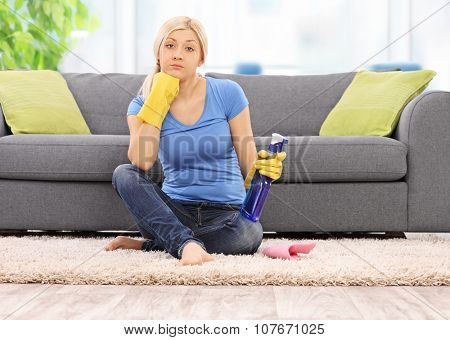 Young woman with yellow cleaning gloves holding a spray bottle and sitting in front of a gray sofa at home shot with tilt and shift lens