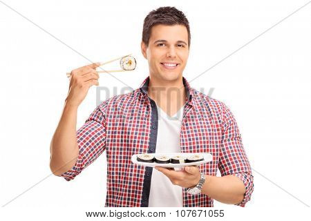 Studio shot of a young man holding a piece of sushi on Chinese sticks isolated on white background