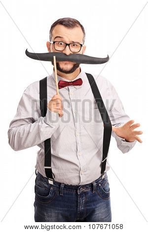 Vertical shot of a young male hipster holding a fake mustache and looking at the camera isolated on white background
