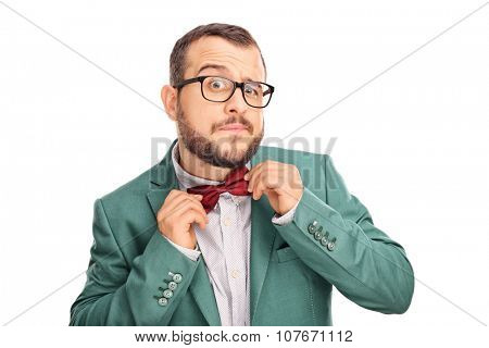 Studio shot of a young male hipster adjusting his bow-tie in a mirror isolated on white background