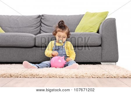 Cute little baby girl putting a coin into a pink piggybank seated in front of a gray sofa isolated on white background
