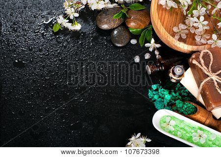 Spa concept on a dark background. Sea salt, flowering branches of cherry, aromatic oils