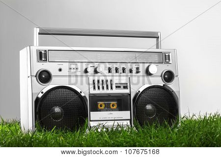 Retro-styled Silver Boom Box Over Green Grass Isolated