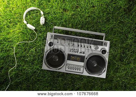 Retro-styled Silver Boom Box And Earphones Over Green Grass Studio Shot