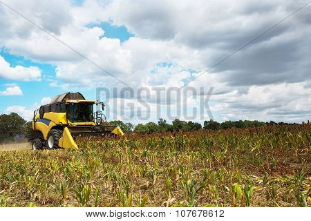 Combine Harvester On Field With A Blue Sky And Fluffy Clouds