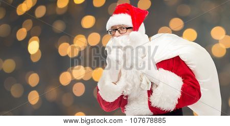 christmas, holidays and people concept - man in costume of santa claus with bag making hush gesture over golden lights background