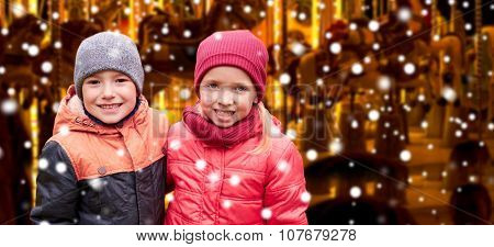 childhood,  holidays winter, christmas, friendship and people concept - happy little girl and boy over snow and carousel background