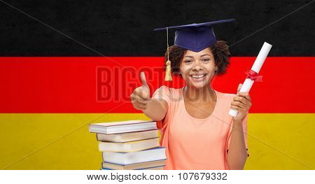 education, school, graduation, gesture and people concept - happy smiling african american student girl in bachelor cap with books and diploma showing thumbs up over german flag background