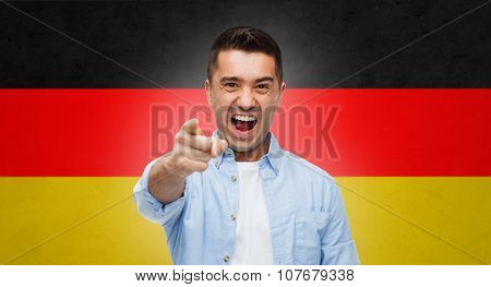 emotions, patriotism, citizenship, gesture and people concept - angry man shouting and pointing finger on you over german flag background