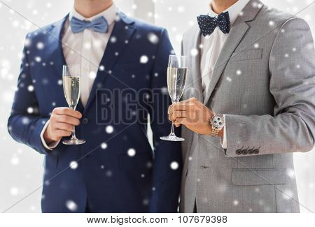 people, celebration, homosexuality, same-sex marriage and love concept - close up of married male gay couple in suits and bow-ties drinking sparkling wine from glasses on wedding over snow effect