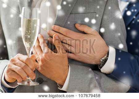 people, celebration, homosexuality, same-sex marriage and love concept - close up of happy married male gay couple in suits drinking sparkling wine from glass on wedding over snow effect