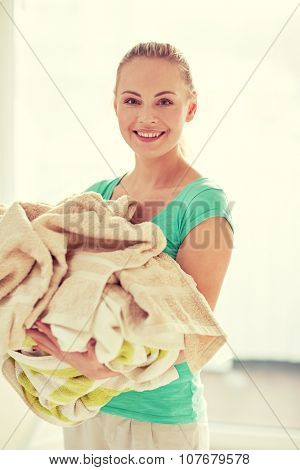people, housework, laundry and housekeeping concept - happy woman carrying washed clothes at home