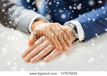people, homosexuality, same-sex marriage and love concept - close up of happy male gay couple hands with wedding rings on over snow effect