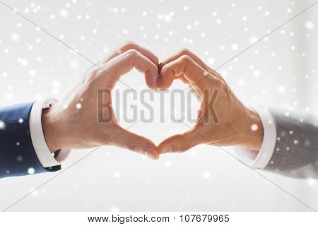 people, homosexuality, same-sex marriage, gesture and love concept - close up of happy male gay couple hands showing heart hand sign over snow effect