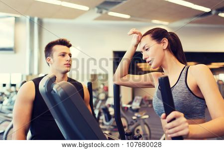 sport, fitness, lifestyle, technology and people concept - tired woman with trainer exercising on stepper in gym