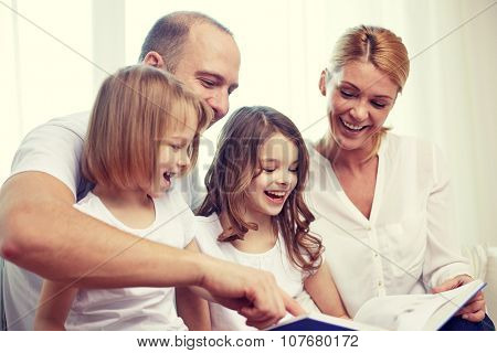 family, childhood, holidays and people - smiling mother, father and little girls reading book at home