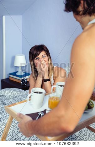 Surprised woman in bed looking to man bringing breakfast