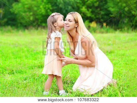 Little Daughter Child Kissing Loving Mother In Summer Day, Happy Family Outdoors