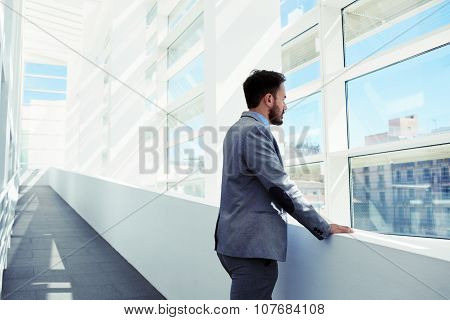 Young intelligent male lawyer thinking about something while looking in big office window