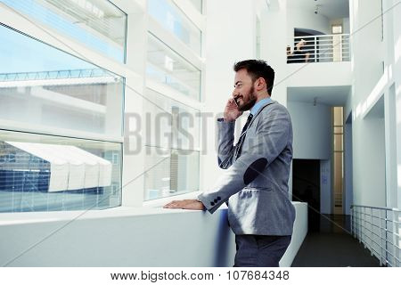 Handsome intelligent male economist calling on cell telephone during work break