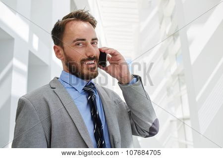 cheerful intelligent male economist dressed in luxury suit speaking on cell telephone