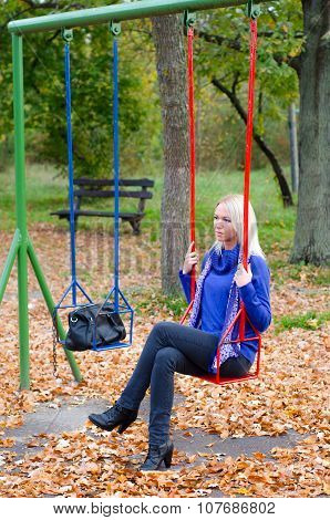 Sad Girl Sitting On The Swing In The Park On Colorful Autumn Day