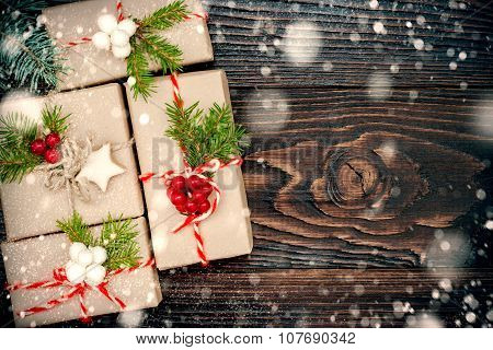 Christmas presents in boxes on a wooden background with copy space. Drawn snowfall. Toned