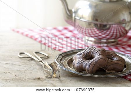 Christmas Chocolate Gingerbread On A Silver Plate, Cake Tongs And Teapot On A Wooden Table