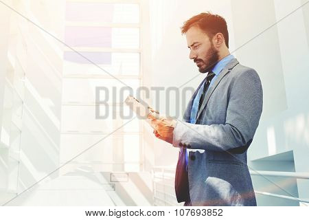 Confident man economist holding digital tablet while standing in modern office corridor