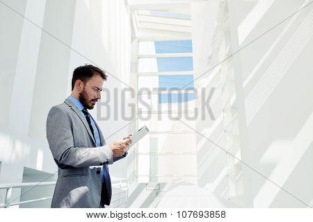 Successful man office worker in formal wear use digital tablet after meeting