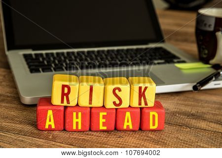 Risk Ahead written on a wooden cube in a office desk