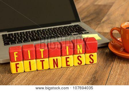 Fit in Fitness written on a wooden cube in a office desk