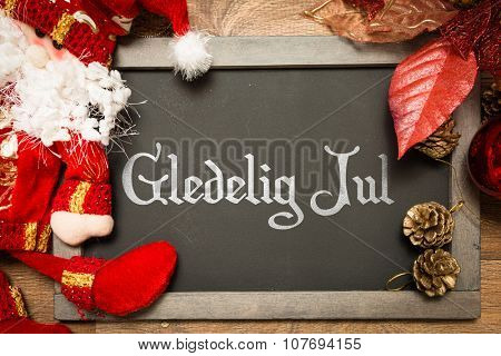Blackboard with the text: Happy Christmas (in Norwegian) in a conceptual image