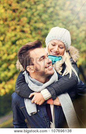 A picture of a young romantic couple piggybacking in the park in autumn