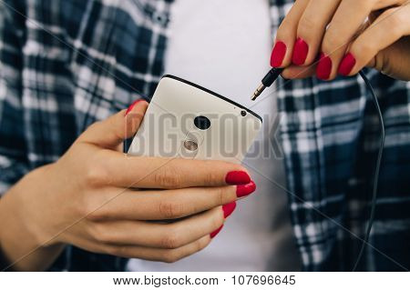 Woman In Plaid Shirt And Red Manicure Connect Headphones To The White Mobile Phone