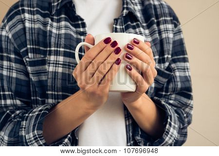 Woman With A Burgundy Manicure In Plaid Shirt Holding White Cup