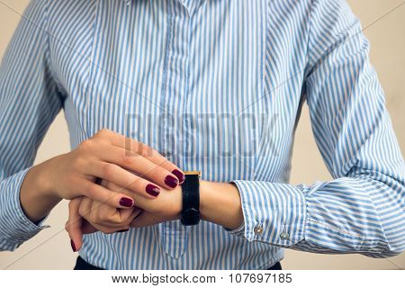 Woman With A Burgundy Manicure In A Blue Striped Shirt Looking The Time On Hand Watch