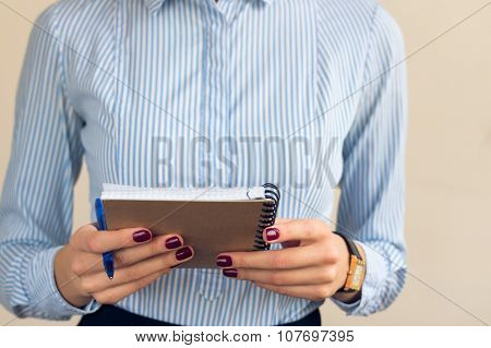 Woman With A Burgundy Manicure In A Blue Striped Shirt Holds Notebook