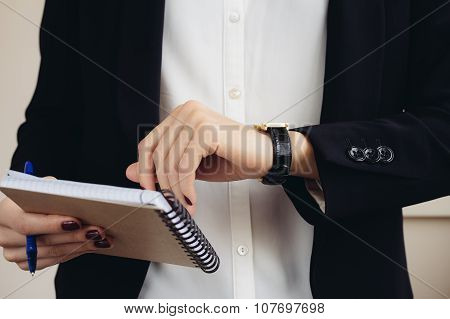 Woman In A Business Suit Holding A Notebook And Looks At Her Watch Close-up