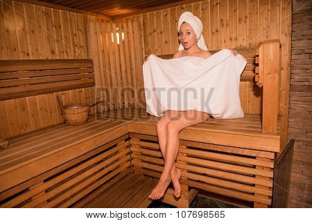 Surprised Girl In Towel Sitting On The Bench In Sauna