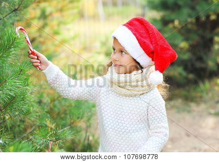 Christmas And People Concept - Child In Santa Red Hat With Sweet Lollipop Cane And Tree