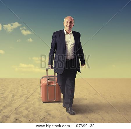 smiley walking senior man with suitcase in a desert
