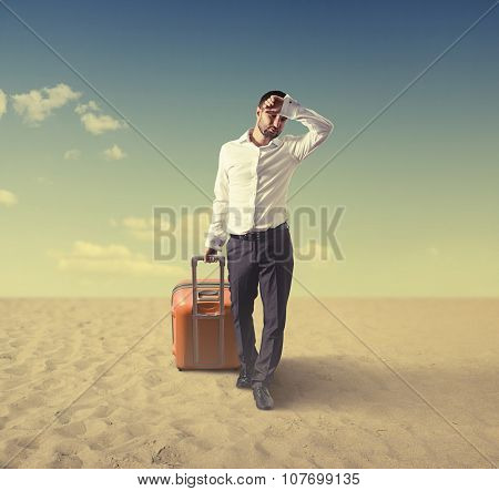 tired young businessman with suitcase walking in a desert