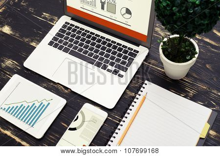top view of workspace with laptop, smartphone, tablet pc with diagram and notebook