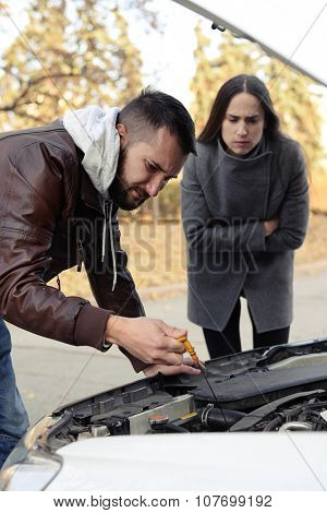 worried couple looking under the hood of breakdown car at outdoor