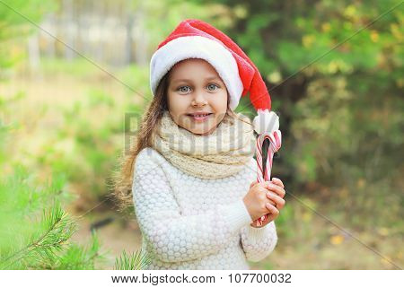 Christmas And People Concept - Portrait Little Girl Child In Santa Red Hat With Sweet Lollipop Cane