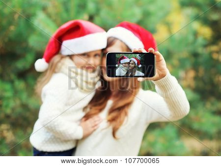 Christmas And Technology Concept - Mother And Child Taking Picture Self Portrait On Smartphone Toget