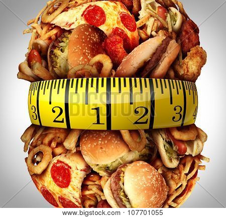 Obesity waistline diet concept as a group of unhealthy fast food as hamburgersfries and hot dogs bulging out as a fat stomach with a tape measure wrapped around the greasy food.