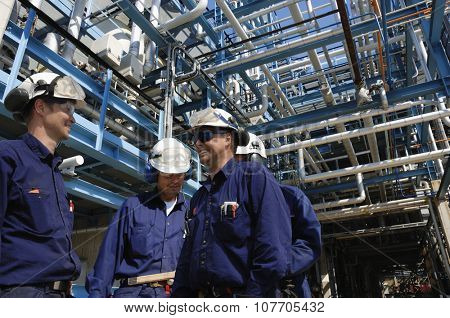 oil and gas workers inside large pipelines constructions, chemical refinery industry