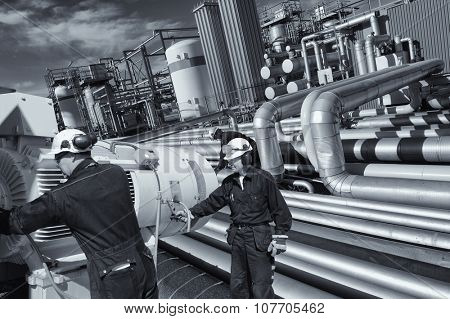 giant pipeline construction, engineer checking for leaks inside refinery
